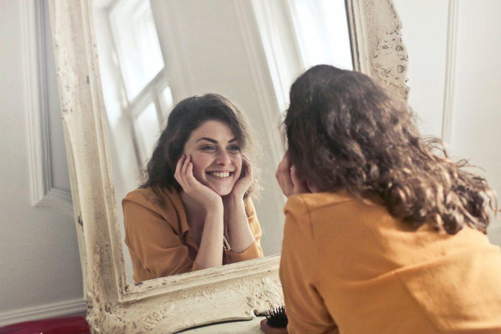 Kvinde smiler i spejl